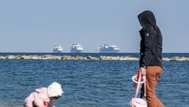 امرأة تراقب طفلاً يلعب على طول شاطئ في مدينة ليماسول جنوبي قبرص (أ ف ب).
