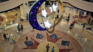 أشخاص يمشون داخل مركز تسوق ازدان بزينة رمضان في دبي   بالإمارات العربية المتحدة (28 حزيران 2014، أ ب).