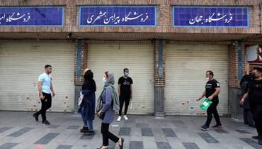 إيرانيون يمرون قبالة محال مقفلة في بازار طهران من جراء قيود كورونا.(أ ف ب)