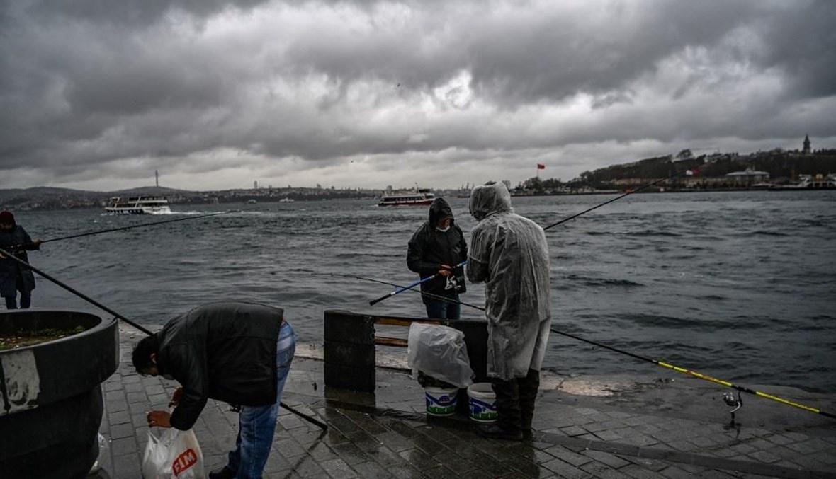 أشخاص يصطادون قرب مضيق البوسفور في أسطنبول في 8 نيسان الجاري.(أ ف ب)