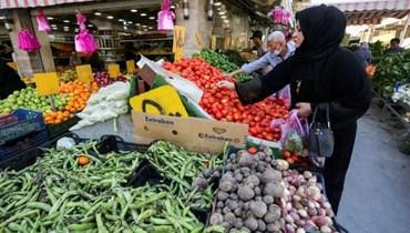 عراقيون يشترون خضارا من محل في بغداد الأحد.(أ ف ب)