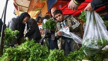 سوريون في أحد أسواق مدينة حلب بشمال سوريا الاحد.(أ ف ب)