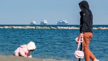 امرأة تراقب طفلاً يلعب على الشاطئ في مدينة ليماسول جنوب قبرص (30 آذار 2021، أ ف ب).