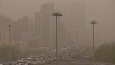 سيارات على طريق خلال عاصفة رملية في بيجينغ (15 نيسان 2021، ا ف ب).
