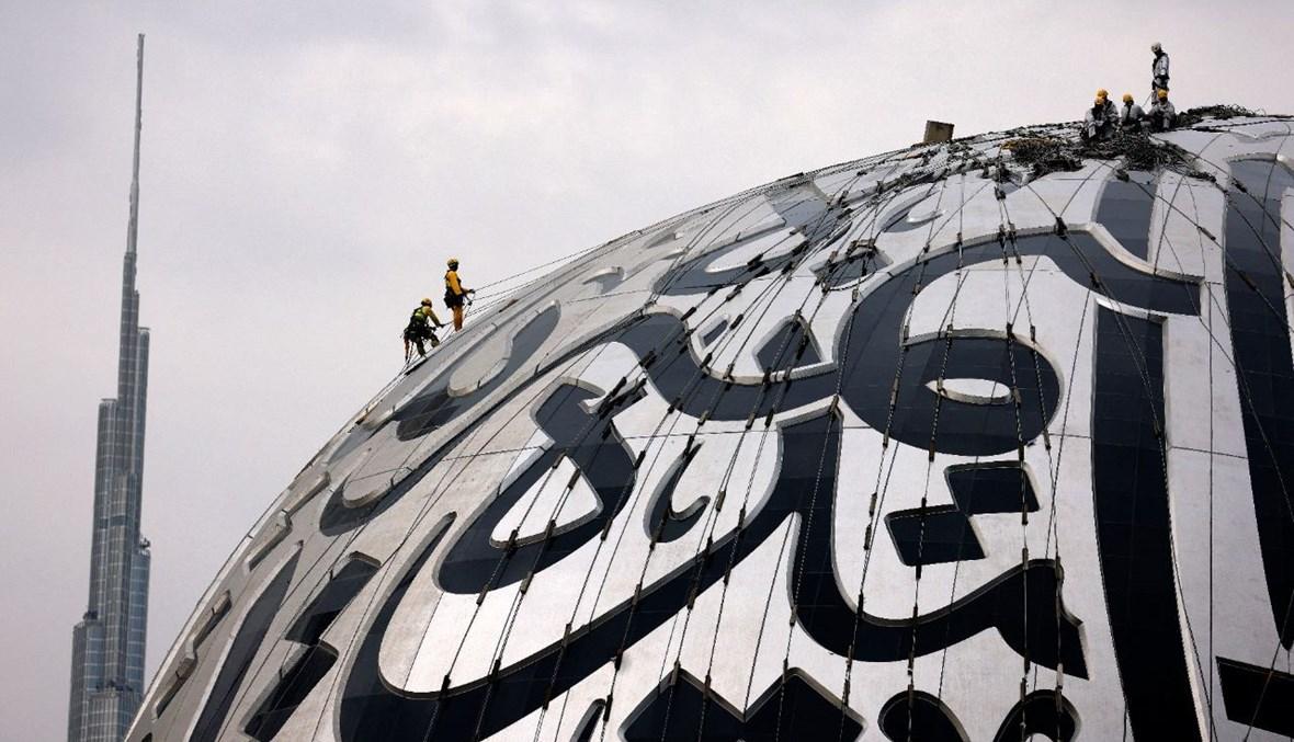 عمال ينظفون واجهة متحف المستقبل الذي هو قيد الإنشاء في دبي بالإمارات (15 نيسان 2021، ا ف ب).