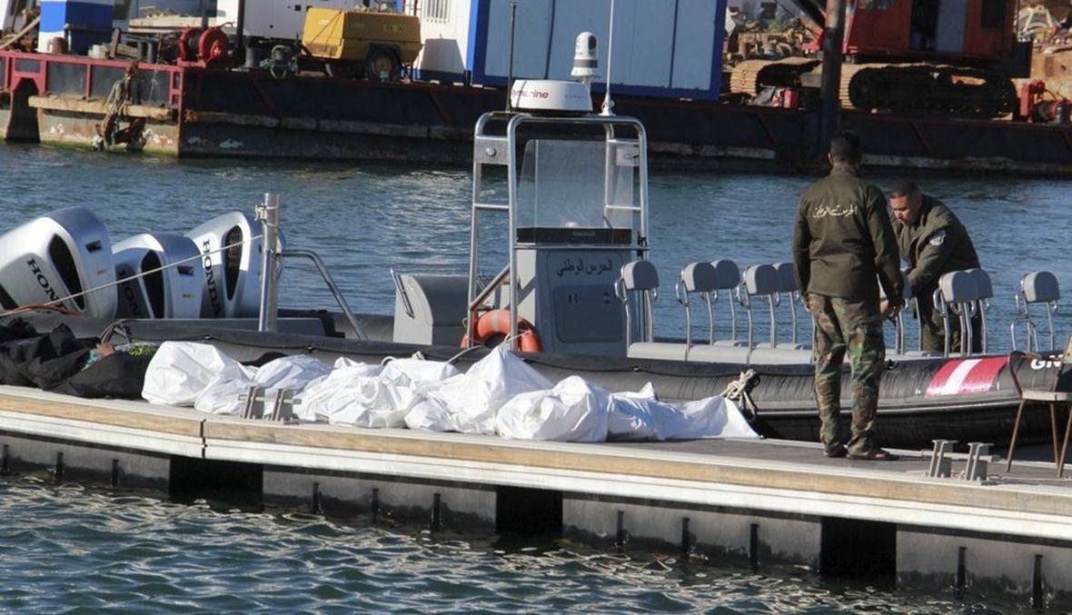 عناصر من خفر السواحل التونسيين يقفون قرب جثث مهاجرين في ميناء صفاقس وسط تونس (24 ك1 2020، أ ب).