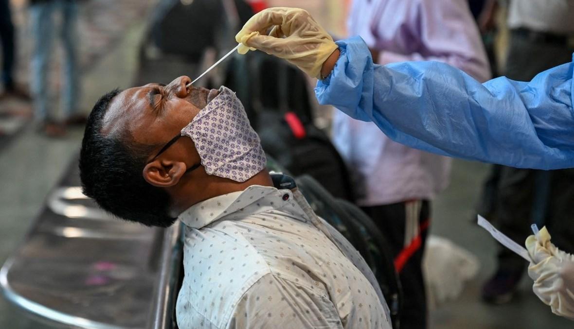 عامل صحي يأخذ مسحة أنفية من أحد الركاب بعد وصوله إلى محطة قطارات في مومباي بالهند (16 نيسان 2021، أ ف ب).