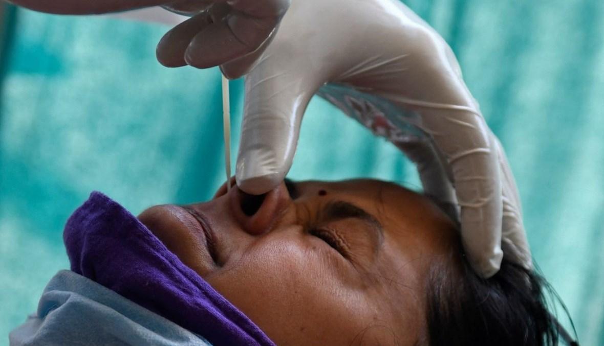 عامل صحي يأخذ مسحة أنفية من امرأة في أمريتسار بالهند (18 نيسان 2021، أ ف ب).