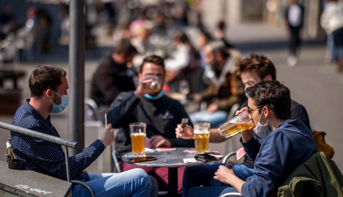 أشخاص يستمتعون باحتساء الجعة في لوزان (19 نيسان 2021، أ ف ب).