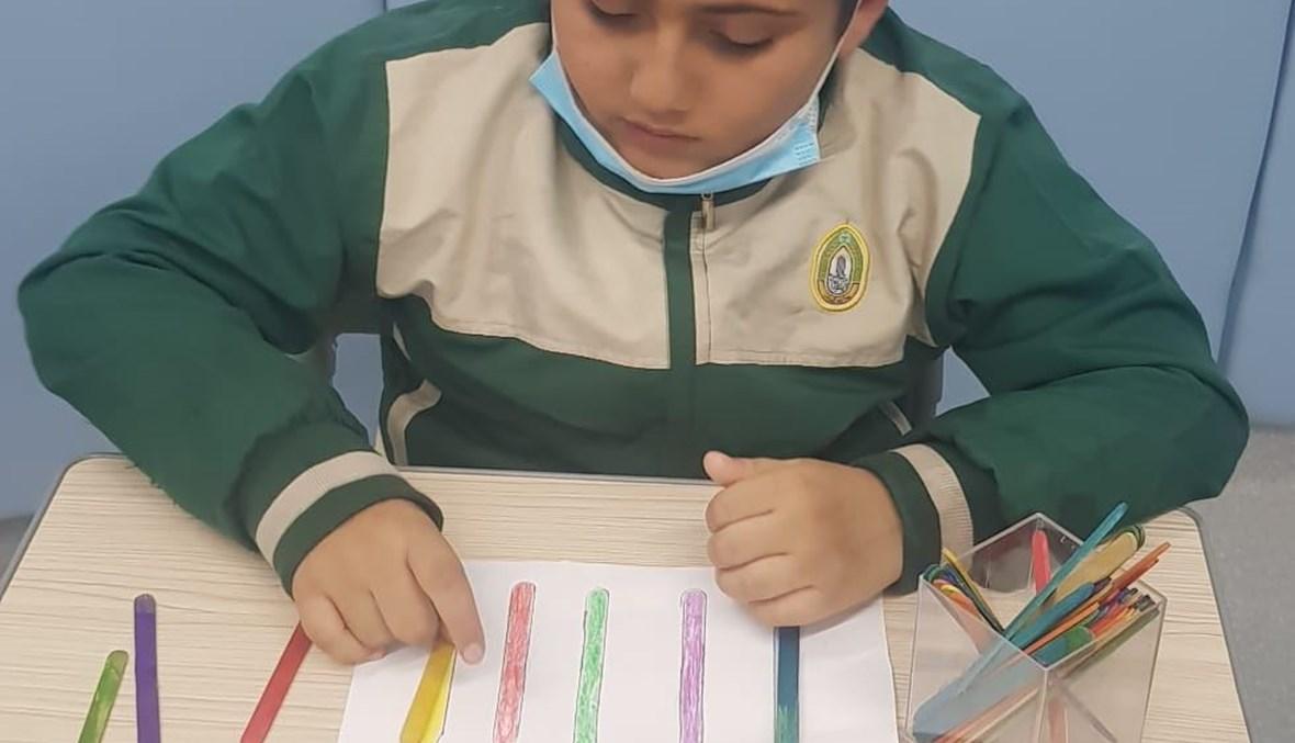 طفل لديه إضطراب طيف التوحد خلال حصة تربوية .