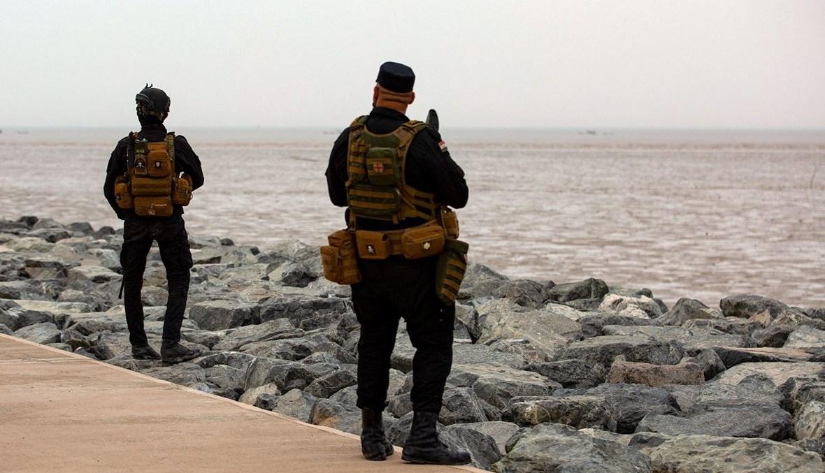 عنصران من قوات الأمن العراقية في حراسة، أثناء زيارة رئيس الوزراء العراقي للمشاركة في احتفال بالبصرة، لوضع حجر الأساس لمشروع ميناء الفاو الكبير (أ ف ب- 11 نيسان 2021).