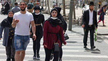 أشخاص يمشون من دون كمامات في أحد شوارع القدس (18 نيسان 2021، ا ف ب).