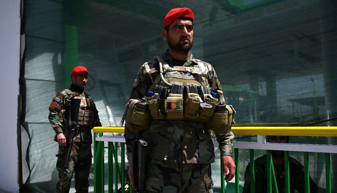 جنديان افغانيان وقفا بالقرب من محطة بنزين تضررت من جراء هجوم بقنبلة في كابول (21 نيسان 2021، أ ف ب).