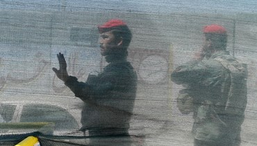 جنود أفغان يقفون بالقرب من موقع هجوم بقنبلة في كابول (21 نيسان 2021، أ ف ب).