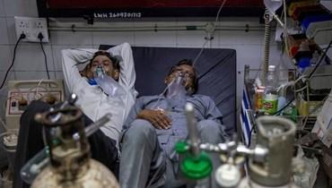 مصابان بكورونا يتشاركان سريراً واحداً في أحد مستشفيات نيودلهي.