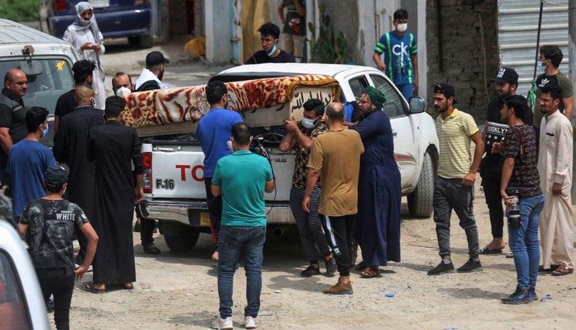 أقارب يتسلمون جثمان إحدى ضحايا الحريق في مستشفى أبن الخطيب في بغداد أمس. (أ ف ب)