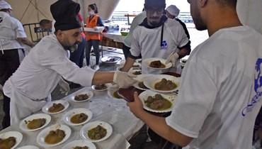 """جمعية """"أمل الجزائر"""" الخيرية توزع وجبات إفطار على المحتاجين في حي باب الواد بالعاصمة الجزائرية.   (أ ف ب)"""