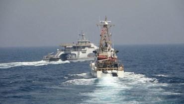 السفينة الأميركية وزوارق إيرانية (ا ف ب)