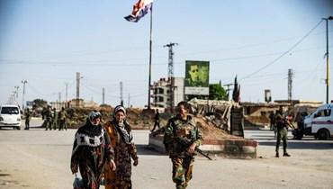 """عنصر من القوات الحكومية السورية يرافق نساء عند حاجز مشترك مع أجهزة الأمن الداخلي الكردية السورية المعروفة بـ""""الأسايش"""" في حي الطي بمدينة القامشلي شمال شرق سوريا (27 نيسان 2021، أ ف ب)."""