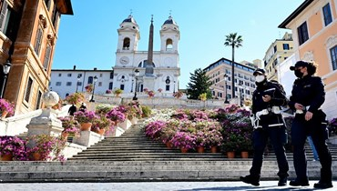 شرطيان يقومان بدورية في ساحة بيازا دي سبانيا في روما (23 نيسان 2021، أ ف ب).