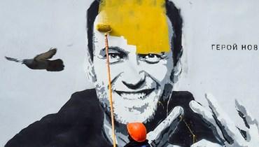 عامل يطلي رسماً للمعارض الروسي أليكسي نافالني في مدينة بطرسبرج الروسية الاربعاء.    (أ ف ب)