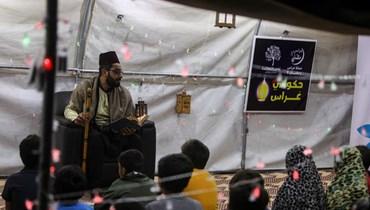 أطفال سوريون من أيتام الحرب يستمعون إلى حكواتي في خيمة أقيمت في مخيم العرمل للنازحين عند أطراف بلدة الدانا شمال غرب محافظة إدلب (29 نيسان 2021، أ ف ب).