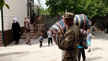 موظف في وزارة الطوارئ في قيرغيزستان يحمل فرشات لمواطنين في باتكين، بعد إجلائهم من المناطق المتاخمة لطاجيكستان (30 نيسان 2021، أ ف ب).