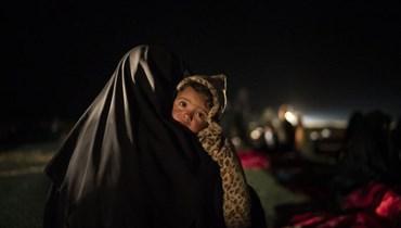 امرأة تحمل طفلها في مركز تديره قوات سوريا الديموقراطية خارج الباغوز بسوريا (25 شباط 2019، أ ب).
