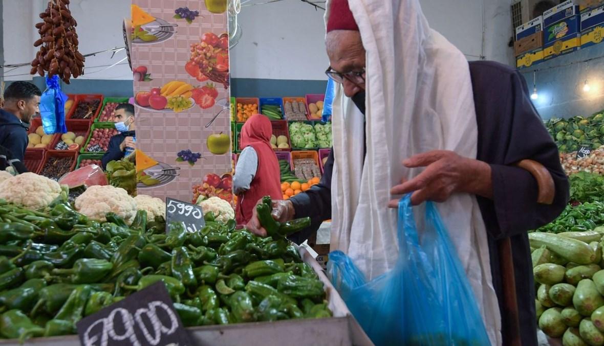 رجل يشتري الخضار في السوق المركزية في بلدة مساكن شمال شرق تونس (24 نيسان 2021، أ ف ب).