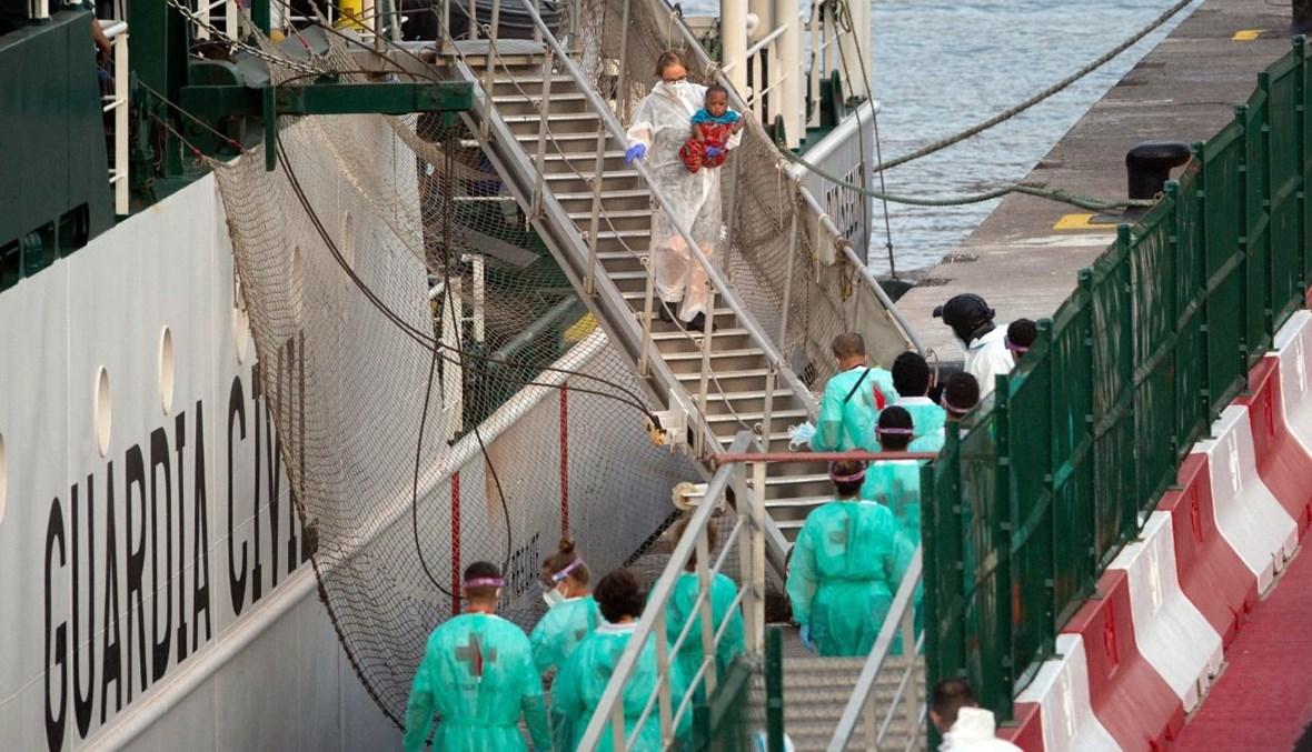 مهاجرون لدى وصولهم إلى بويرتو دي لوس كريستيانوس في جزيرة تينيريفي الإسبانية على متن سفينة تابعة للحرس المدني في أرونا (27 نيسان 2021، أ ف ب).