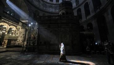 امرأة من الأرثوذكس الإثيوبيين في المكان الذي يُعتقد أن يسوع المسيح دفن فيه، خلال احتفالات أحد الشعانين في كنيسة القيامة في القدس (25 نيسان 2021، أ ف ب).