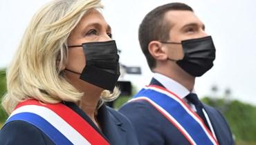زعيمة اليمين المتطرف مارين لوبان ورئيس حزب التجمع الوطني اليميني المتطرف يوروديبوتي جوردان بارديلا، يضعان إكليلًا من الزهور أمام تمثال جان داركفي باريس (أ ف ب).
