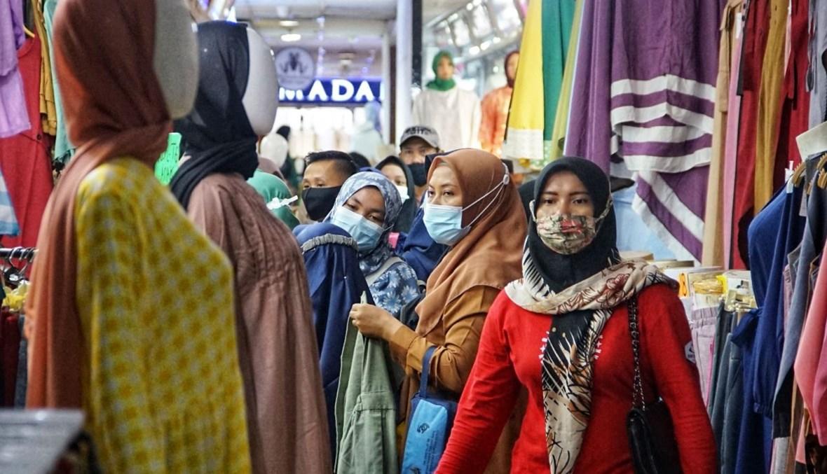 أشخاص يتسوقون في سوق الجملة في تاناه أبانغ في جاكرتا قبل احتفالات عيد الفطر (3 ايار 2021، أ ف ب).