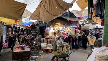أشخاص يتسوقون في سوق في صنعاء (2 ايار 2021، أ ف ب).