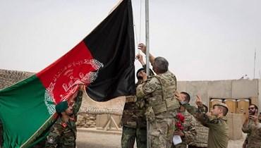 جنود أميركيون وأفغان يرفعون العلم الأفغاني خلال احتفال تسليم في معسكر أنتونيك في ولاية هلمند (2 ايار 2021، أ ف ب).