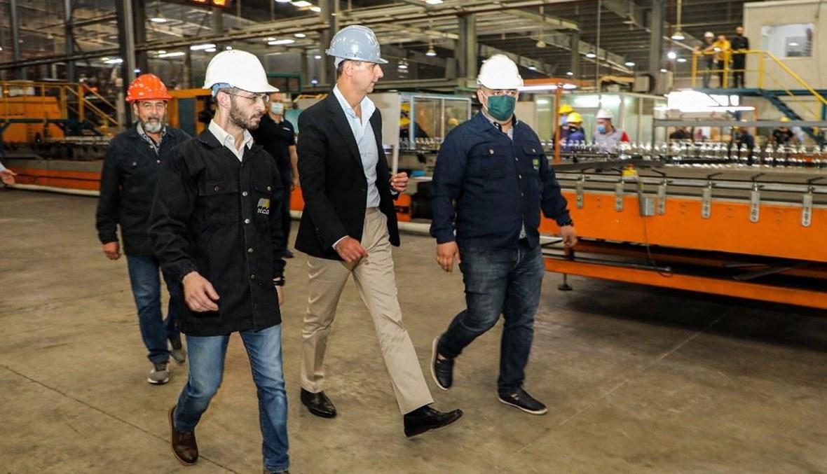 الرئيس السوري بشار الاسد خلال جولة في منطقة حسياء الصناعية بحمص أمس.   (أ ف ب)