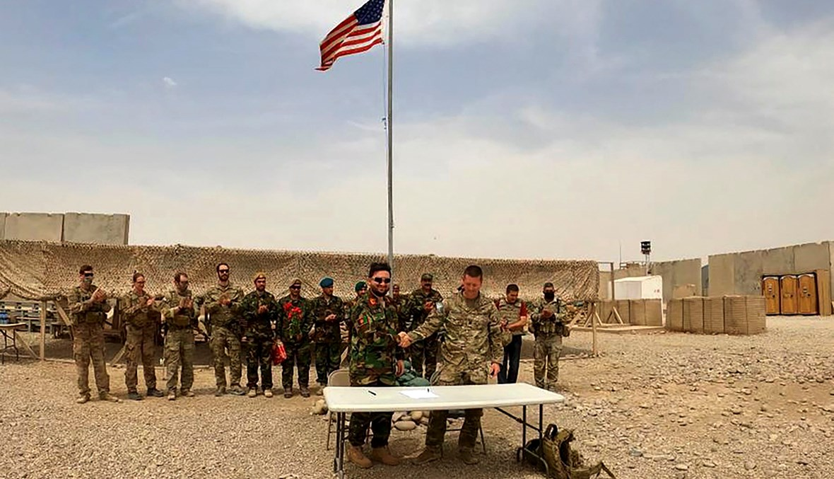 جندي أميريكي وآخر من الجيش الوطني الأفغاني يتصافحان خلال مراسم تسليم الجيش الأفغاني فيلق 215 مايواند في معسكر أنتونيك. في ولاية هلمند (أ ف ب).