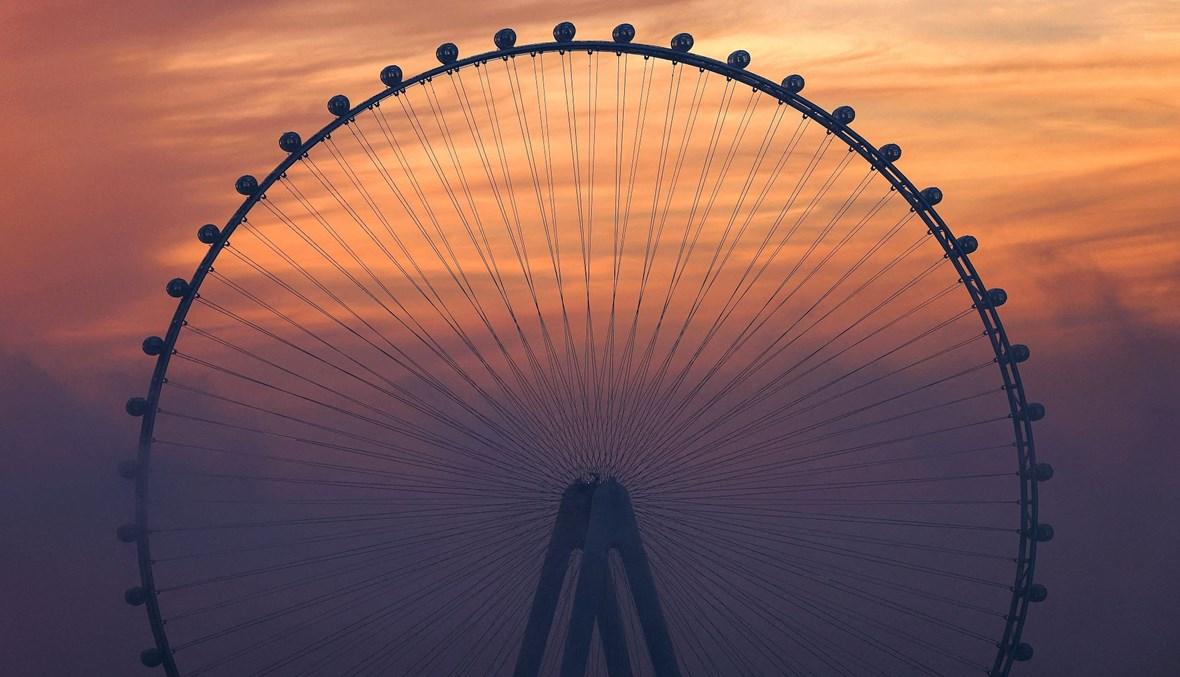 """عجلة """"فيريس"""" في عين دبي عند غروب الشمس (تعبيرية- أ ف ب)."""