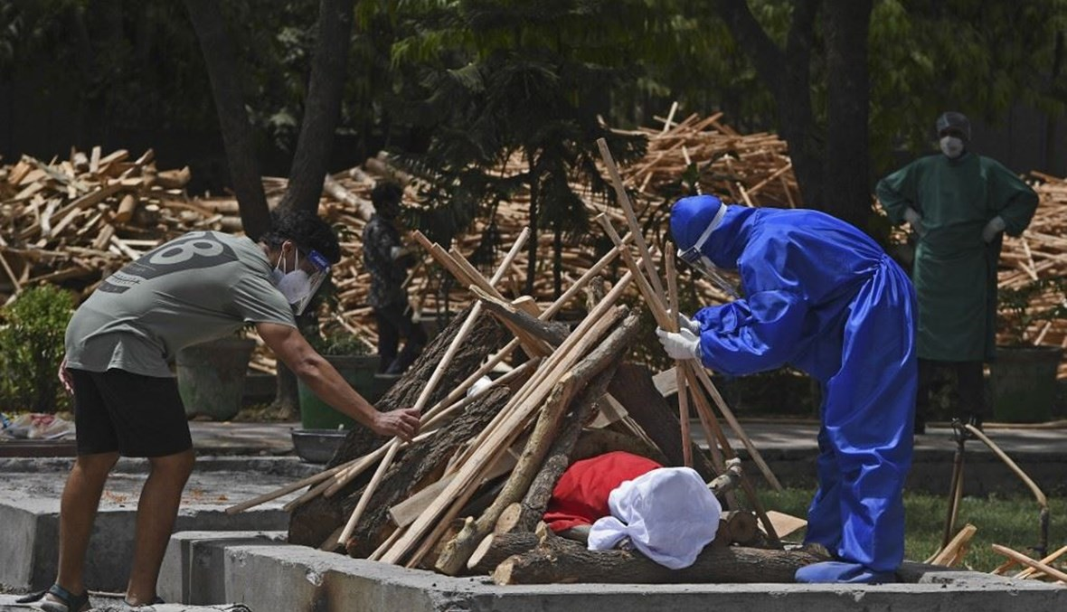 أقارب يجهزون مكاناً لحرق جثة أحد المتوفين بكورونا في نيودلهي الاثنين. (أ ف ب)