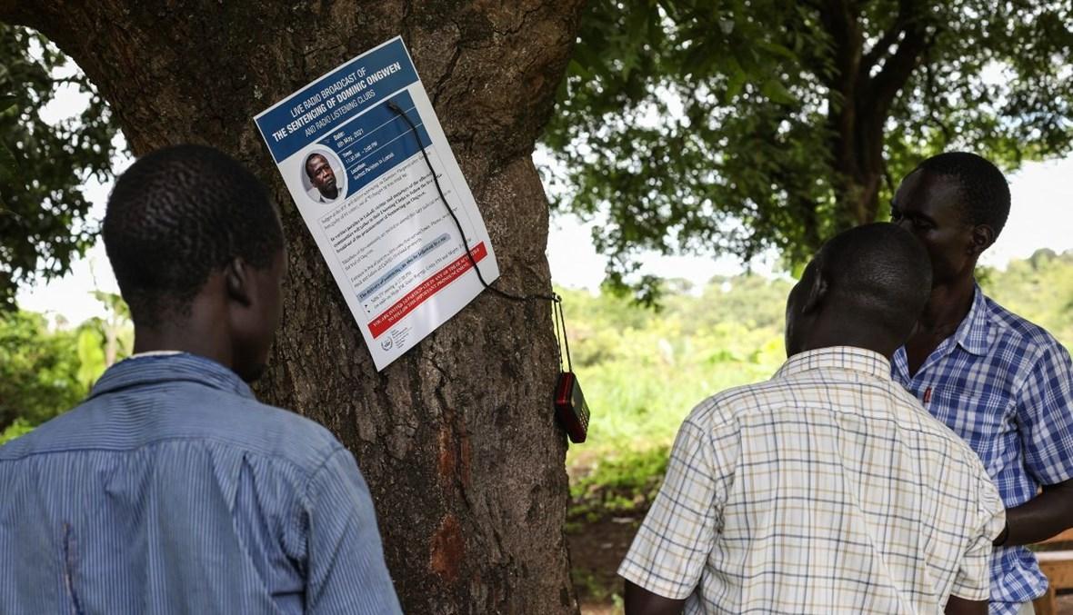 سكان في قرية لوكودي، حيث قُتل العشرات في عام 2004 على يد جيش الرب للمقاومة، يستمعون إلى حكم المحكمة الجنائية الدولية على أونغوين (6 ايار 2021، أ ف ب).
