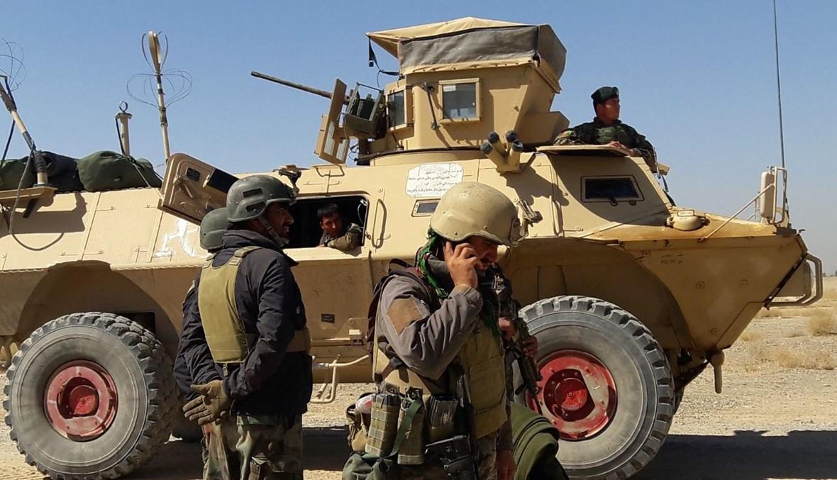 قوات أمن أفغانية تقف بالقرب من مدرعة خلال قتال مع مقاتلي طالبان في منطقة بوشاران بضواحي لشكركاه عاصمة ولاية هلمند (5 ايار 2021، أ ف ب).