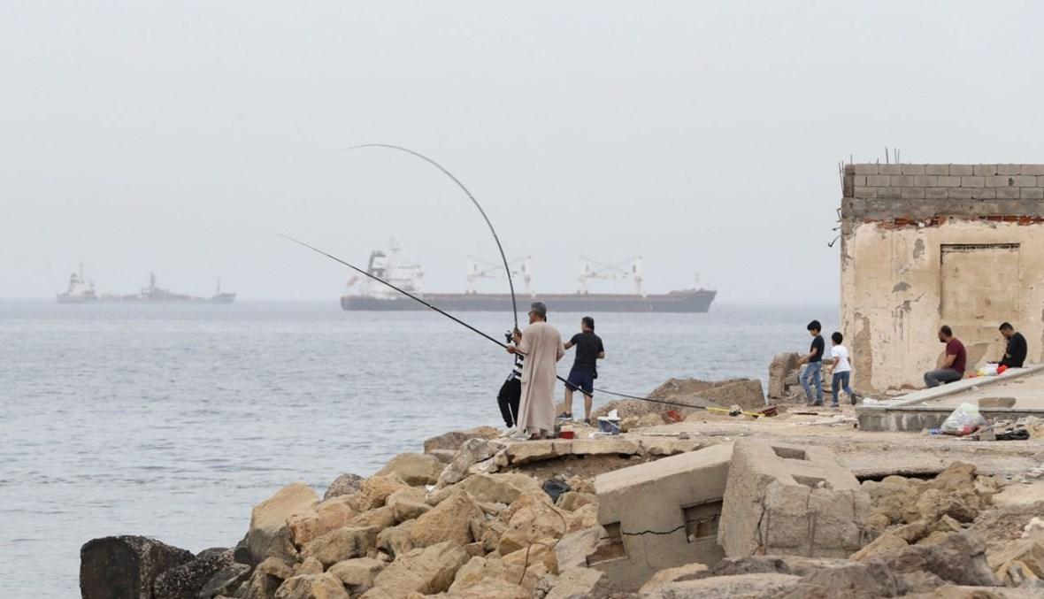 ليبيون يصطادون عند شاطئ في طرابلس (30 نيسان 2021، أ ف ب).