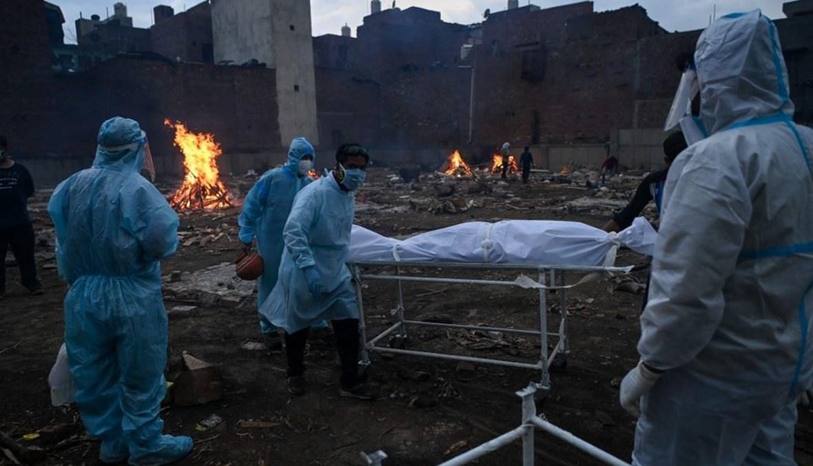 أقارب يحملون جثة أحد المتوفين بكورونا في محرقة بنيودلهي أمس.   (أ ف ب)