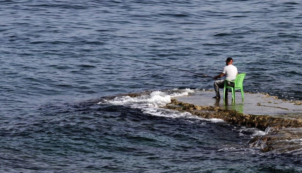 صياد لبناني يجلس على الصخور  في الناقورة (أ ف ب).