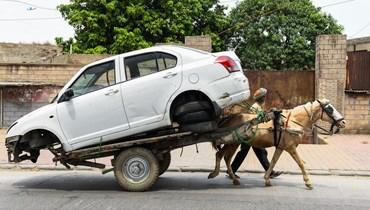 رجل ينقل سيارة على عربة يجرها حصان (تعبيرية - أ ف ب).