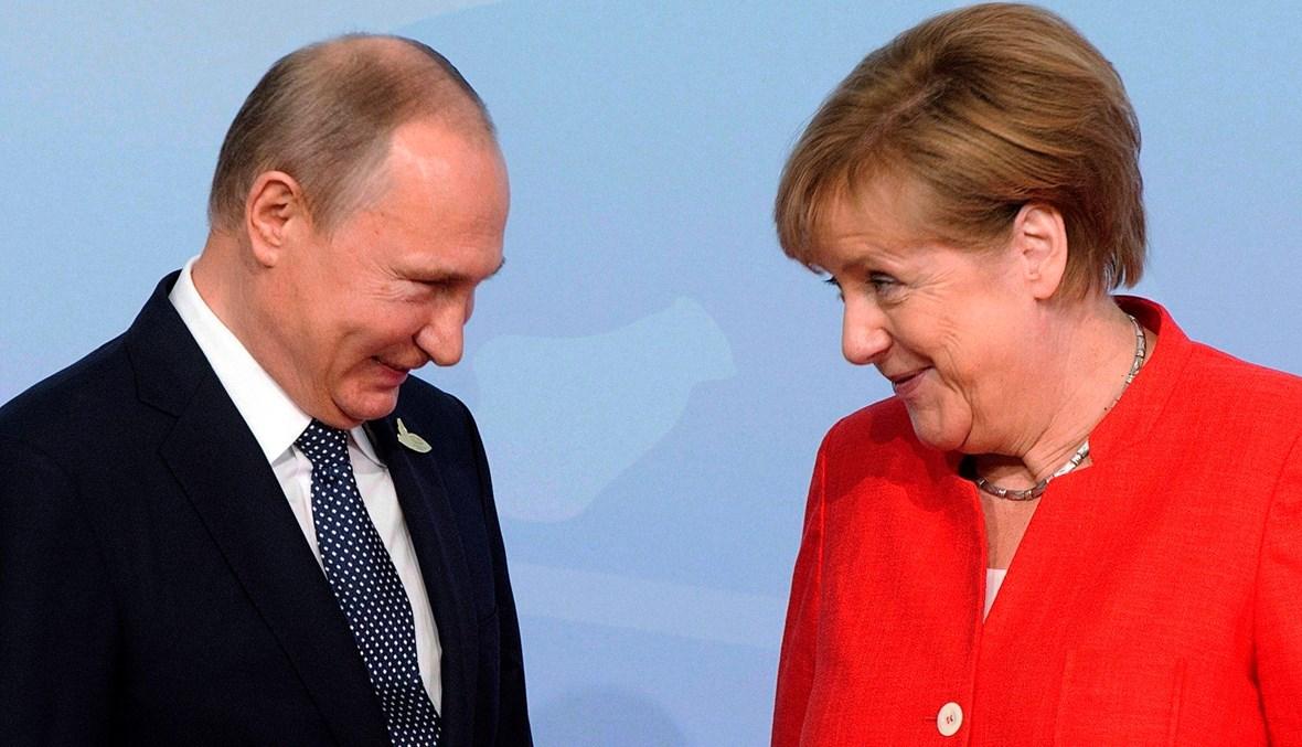 """المستشارة الألمانية أنجيلا ميركل والرئيس الروسي فلاديمير بوتين خلال قمة مجموعة العشرين في هامبورغ - 2017 - """"أ ب"""""""