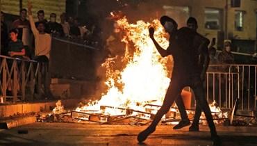 متظاهر فلسطيني يلقي الحجارة على قوات الأمن الإسرائيلية في البلدة القديمة بالقدس (8 ايار 2021، أ ف ب).