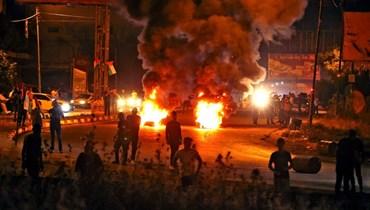 متظاهرون فلسطينيون يحرقون الإطارات خلال اشتباكات مع قوات الأمن الإسرائيلية عند حاجز حوارة جنوب مدينة نابلس في الضفة الغربية المحتلة (8 ايار 2021، أ ف ب).