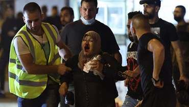 فلسطينيون يساعدون امرأة اصيبت خلال اشتباكات مع قوات الأمن الإسرائيلية في البلدة القديمة بالقدس (8 ايار 2021، أ ف ب).