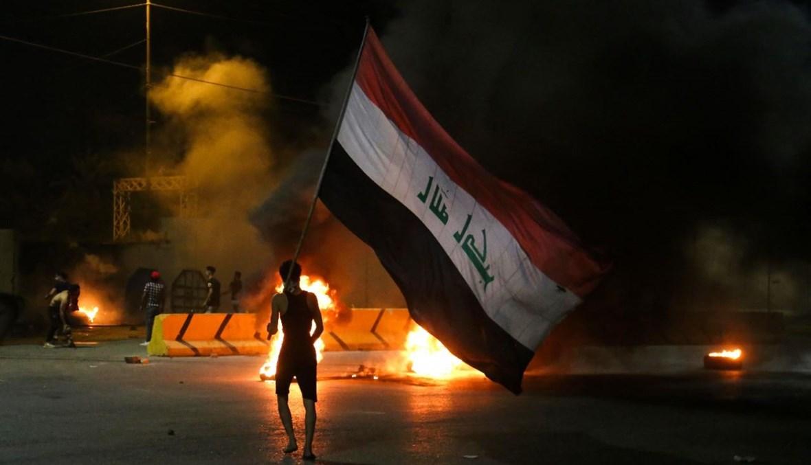 متظاهرون عراقيون يحرقون الإطارات أمام مقر محافظة كربلاء وسط مدينة كربلاء بعد اغتيال الوزني (9 ايار 2021، أ ف ب).